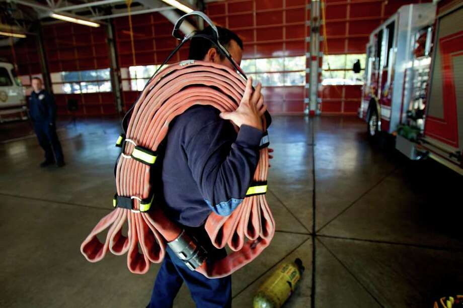 Houston firefighter Jim Bradford carries a hose using a new high-rise hose strap at Fire Station 8 Friday, Nov. 18, 2011, in Houston. Photo: Cody Duty / © 2011 Houston Chronicle