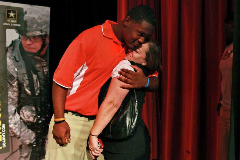 "Javonte Magee hugs Clarice Caldwell, his tutor and ""second mother,"" as he calls her, after he formally accepted his invitation to play in the U.S. Army All-American Bowl at Sam Houston High School in San Antonio on Wednesday, Nov. 16, 2011. Photo: LISA KRANTZ, Express-News"