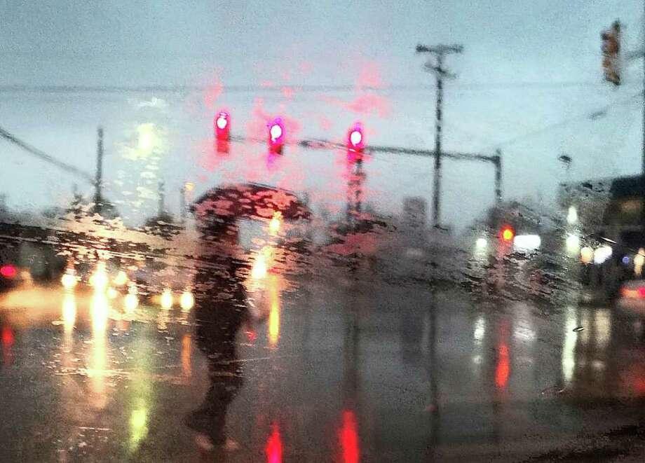A pedestrian crosses Blanco Avenue during a rainstorm in San Antonio Texas on Tuesday, November 15, 2011. Photo: BILLY CALZADA, Express-News