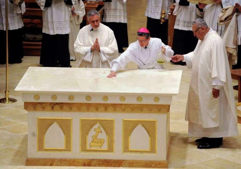 San Antonio Archbishop Gustavo Garcia-Siller spreads Chrism oil on the new altar at San Fernando