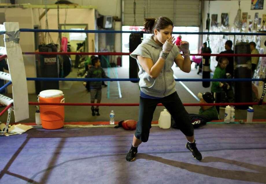 Marlén Esparza se mueve en el cuadrilátero bajo las órdenes de su adiestrador, Rudy Silva, durante una sesión de entrenamiento reciente en el gimnasio del Elite Boxing Club en Houston. Photo: Nick De La Torre / © 2011  Houston Chronicle