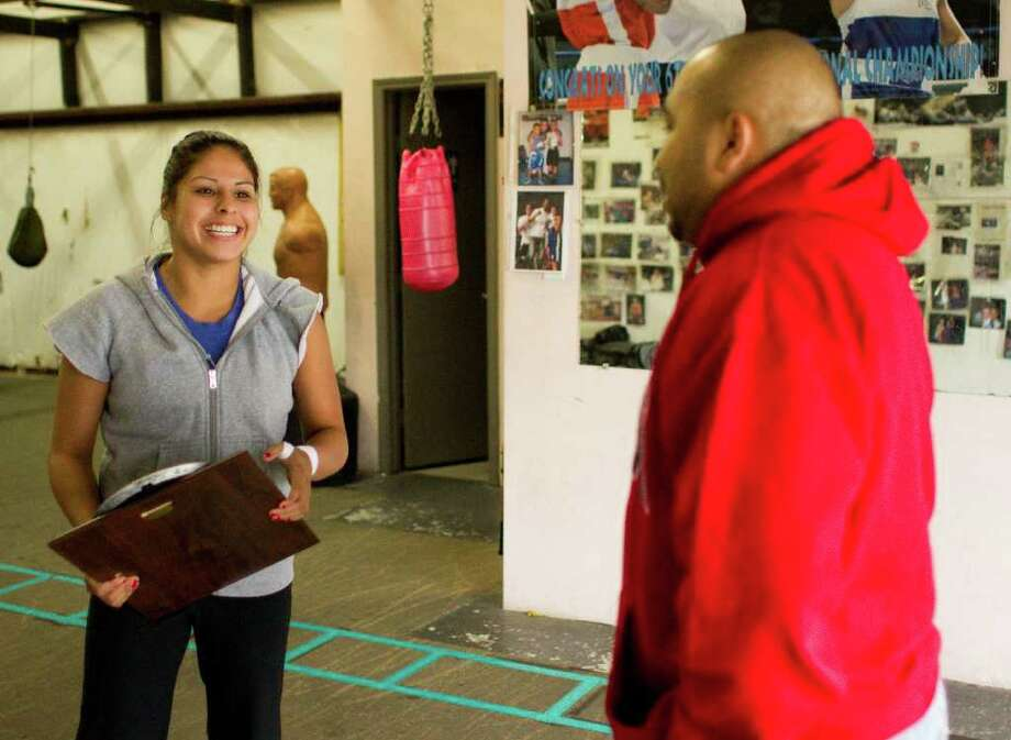 Marlen Esparza, talks with David Donis, owner of Lone Star Hitters Boxing Club, after Donis gave her an award Oct. 28 in the Elite Boxing gym in Houston. Esparza, who's a won five national championships, is hoping to compete in the 2012 Olympics for the U.S. boxing team. Photo: Nick De La Torre / © 2011  Houston Chronicle