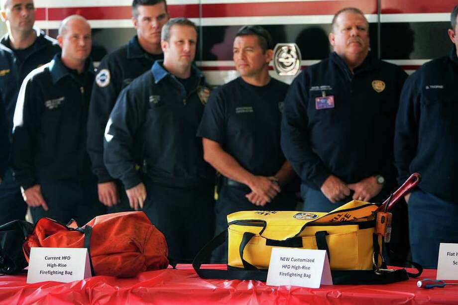 Firefighters stand behind an old and a new high-rise firefighter bag during a press conference at Fire Station 8 Friday, Nov. 18, 2011, in Houston. Chevron presented the Houston Fire Department with $88 thousand of equipment and tools used for high-rise firefighting. Photo: Cody Duty, Houston Chronicle / © 2011 Houston Chronicle