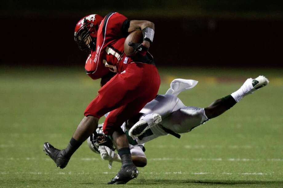 North Shore running back Davonte Milton is brought down by Hightower defensive back Joshua Thomas during the first quarter of high school football playoff action at Abshier Stadium on Friday, Nov. 18, 2011, in Deer Park. Photo: Smiley N. Pool, Houston Chronicle / © 2011  Houston Chronicle