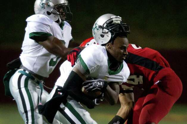 Hightower's Bralon Addison (2) loses his helmet as he is hit by North Shore's Chris Lee (44) during the first quarter of high school football playoff action at Abshier Stadium on Friday, Nov. 18, 2011, in Deer Park. Photo: Smiley N. Pool, Houston Chronicle / © 2011  Houston Chronicle