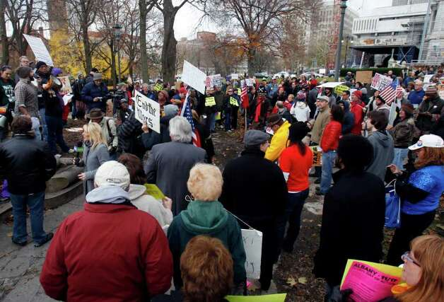 Occupy Albany protesters, joined by Occupy Wall Street protesters from around the state, rally at Lafayette Park across from the state Capitol in Albany N.Y., on Thursday, Nov. 17, 2011. Activists have also taken their grievances inside the Capitol presenting documents to Gov. Andrew Cuomo's office and the Senate Republican majority urging them to extend the state millionaire's tax. (AP Photo/Mike Groll) Photo: Mike Groll / AP
