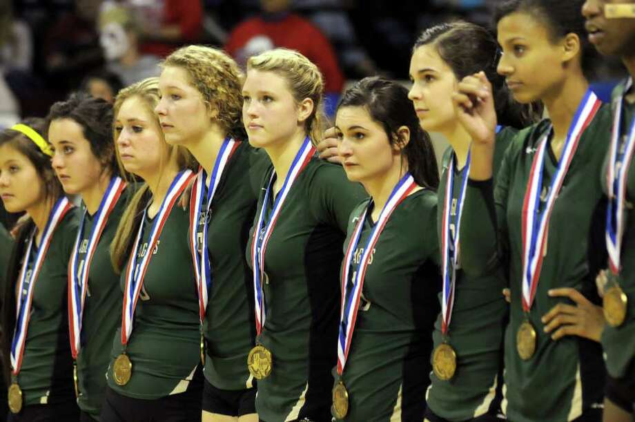 Cy-Falls junior setter Kelly Bailey, center, and her Golden Eagles teammates stand during the medal ceremony after their Class 5A state volleyball semifinal versus McKinney Boyd at Strahan Coliseum on the campus of Texas State University in San Marcos on Friday. Freelance photo by Jerry Baker Photo: Jerry Baker, For The Chronicle
