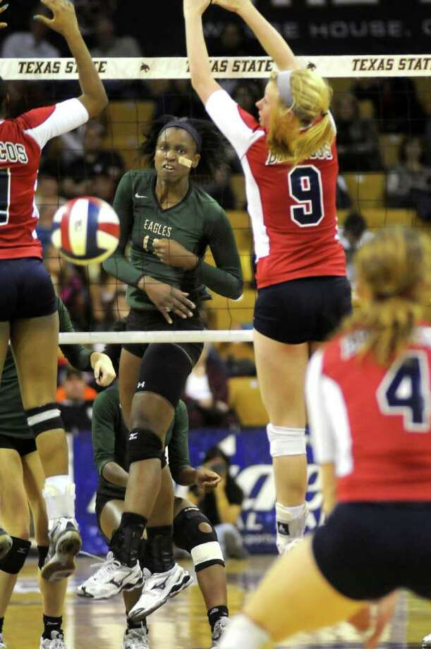 Cy-Falls senior Alexis Austin, center, sends a kill between McKinney Boyd's Megan Mollett, left, and Krista Bucovec (#9) during their Class 5A state volleyball semifinal at Strahan Coliseum on the campus of Texas State University in San Marcos on Friday. Freelance photo by Jerry Baker Photo: Jerry Baker, For The Chronicle