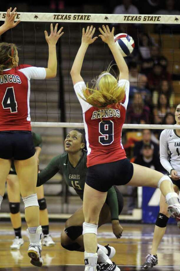Cy-Falls senior Chanel Clark-Bibbs, center, tries to make a pass between McKinney Boyd's Drew Darling (#4) and Krista Bukovec (#9) during the third game of their Class 5A state volleyball semifinal at Strahan Coliseum on the campus of Texas State University in San Marcos on Friday. Freelance photo by Jerry Baker Photo: Jerry Baker, For The Chronicle