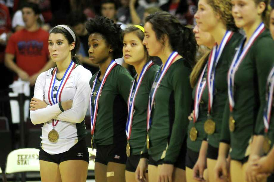 Cy-Falls senior Libero Brittnee Dawley, left, and her Golden Eagles teammates stand during the medal ceremony after their Class 5A state volleyball semifinal versus McKinney Boyd at Strahan Coliseum on the campus of Texas State University in San Marcos on Friday. Freelance photo by Jerry Baker Photo: Jerry Baker, For The Chronicle