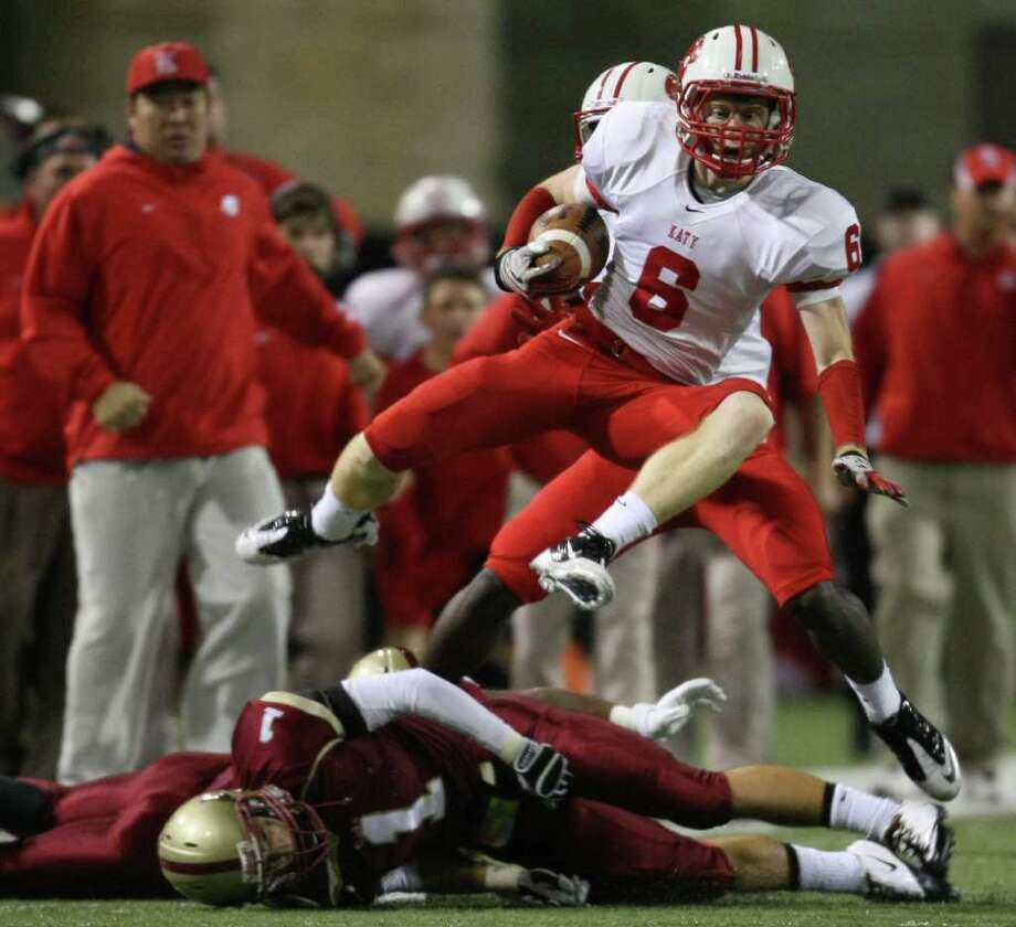 Katy's Branson Ebrecht (6) leaps over Cypress Woods' Mason Roberts (1) during the first half of an area playoff game, Friday, November 18, 2011 at Berry Center in Cypress. Photo: Eric Christian Smith, For The Chronicle