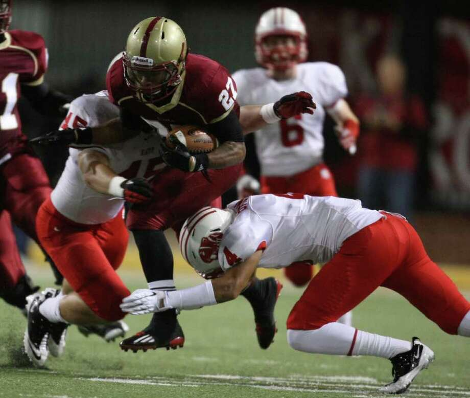 Cypress Woods' Trent Holmes (27) is tackled by Katy's Jake Blomstrom (45) and Isaiah Brown during the first half of an area playoff game, Friday, November 18, 2011 at Berry Center in Cypress. Photo: Eric Christian Smith, For The Chronicle