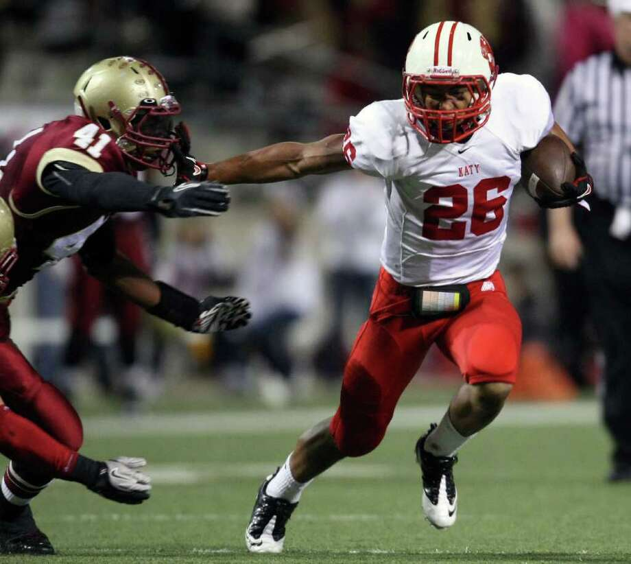 Katy's Rodney Anderson (26) fends off Cypress Woods' Deoundrie Davis during the first half of an area playoff game, Friday, November 18, 2011 at Berry Center in Cypress. Photo: Eric Christian Smith, For The Chronicle