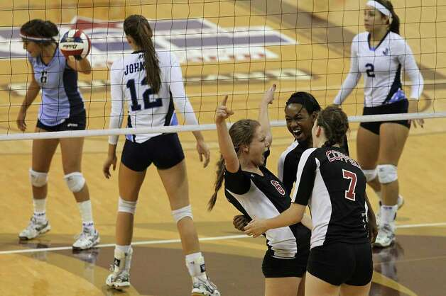 Coppell's Cassidy Pickrell (06) gets congratulated by teammates Kierra Holst (07) and Chiaka Obgogu (11) after winning a point against Johnson in the 5A State Semifinals in volleyball at Strahan Coliseum in San Marcos on Friday, Nov. 18, 2011. Johnson lost in five games to Coppell to end their season. Photo: Kin Man Hui, ~ / San Antonio Express-News