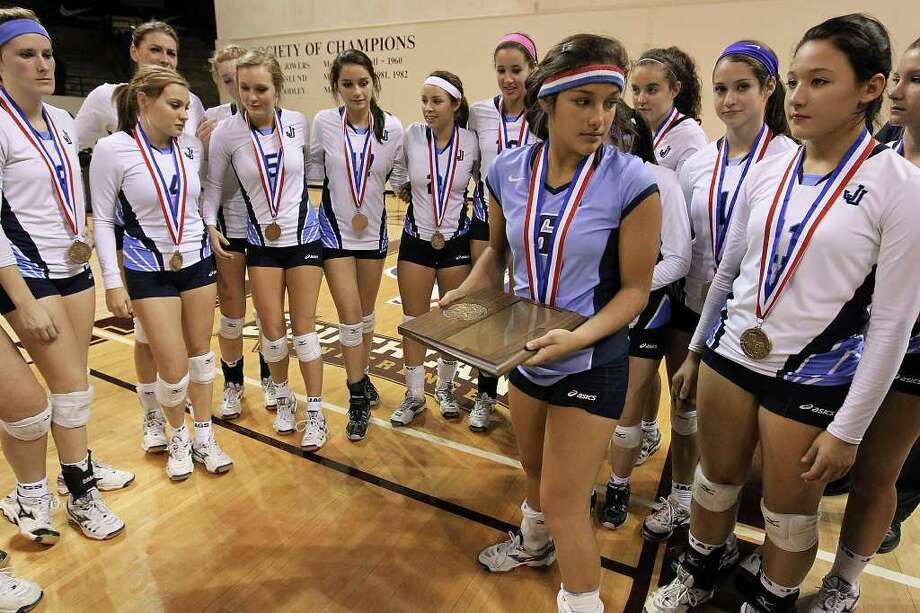 Johnson's Ayssa Garcia (06) holds the semifinalist plaque as the rest of the team reflects on their loss to Coppell in the 5A State Semifinals in volleyball at Strahan Coliseum in San Marcos on Friday, Nov. 18, 2011. Johnson lost in five games to Coppell to end their season. Photo: Kin Man Hui, ~ / San Antonio Express-News