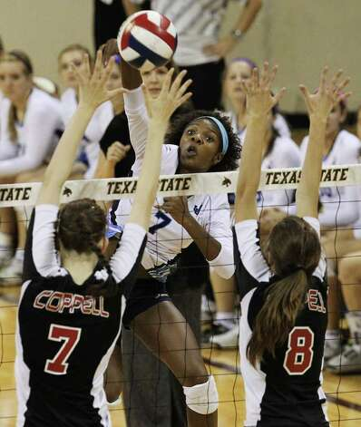Johnson's Carnae Dillard (07) attempts a shot between Coppell's Kierra Holst (07) and Kylie Pickrell (08) in the 5A State Semifinals in volleyball at Strahan Coliseum in San Marcos on Friday, Nov. 18, 2011. Johnson lost in five games to Coppell to end their season. Photo: Kin Man Hui, ~ / San Antonio Express-News