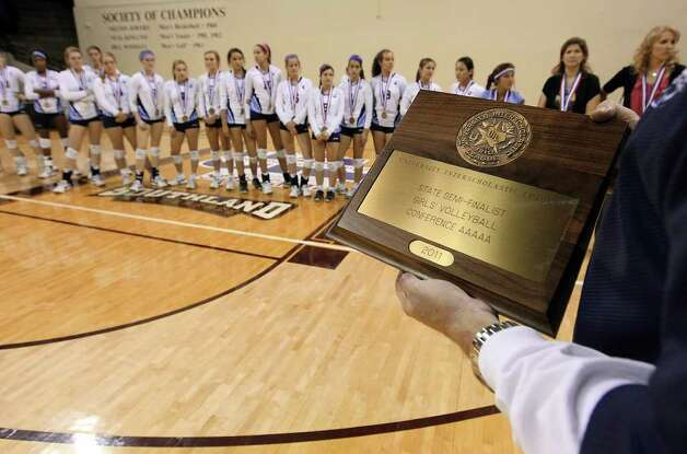 A UIL official holds the semi-finalist plaque to be presented to Johnson over losing to Coppell in the 5A State Semifinals in volleyball at Strahan Coliseum in San Marcos on Friday, Nov. 18, 2011. Johnson lost in five games to Coppell to end their season. Photo: Kin Man Hui, ~ / San Antonio Express-News