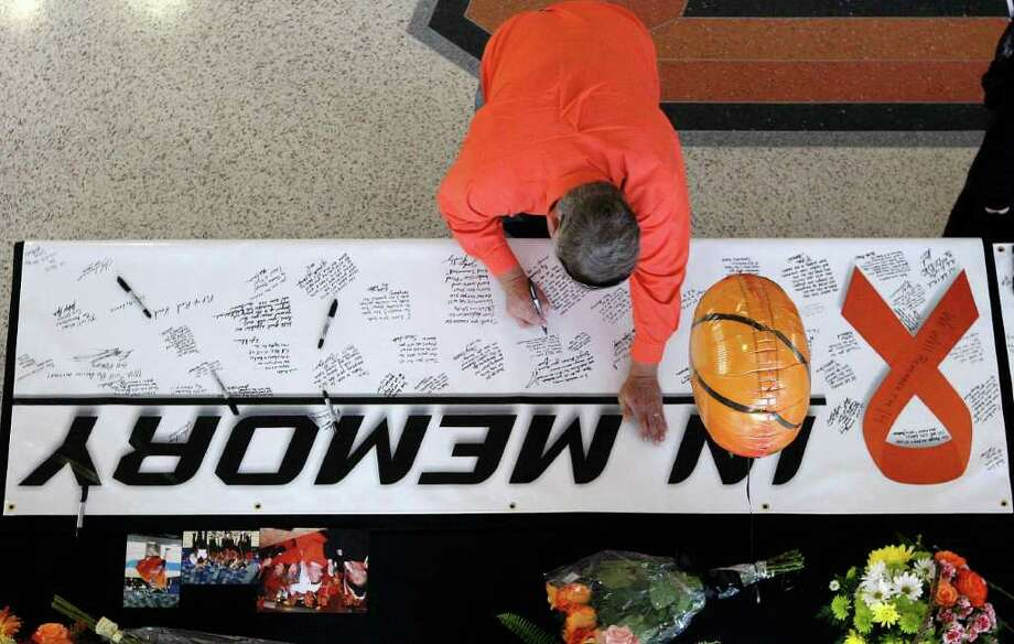 PAYING TRIBUTE: A fan signs a banner in remembrance of Oklahoma State women's basketball coach Kurt Budke and assistant coach Miranda Serna in Stillwater, Okla. Budke and Serna were killed in a plane crash Thursday in Arkansas. Photo: Sue Ogrocki / AP