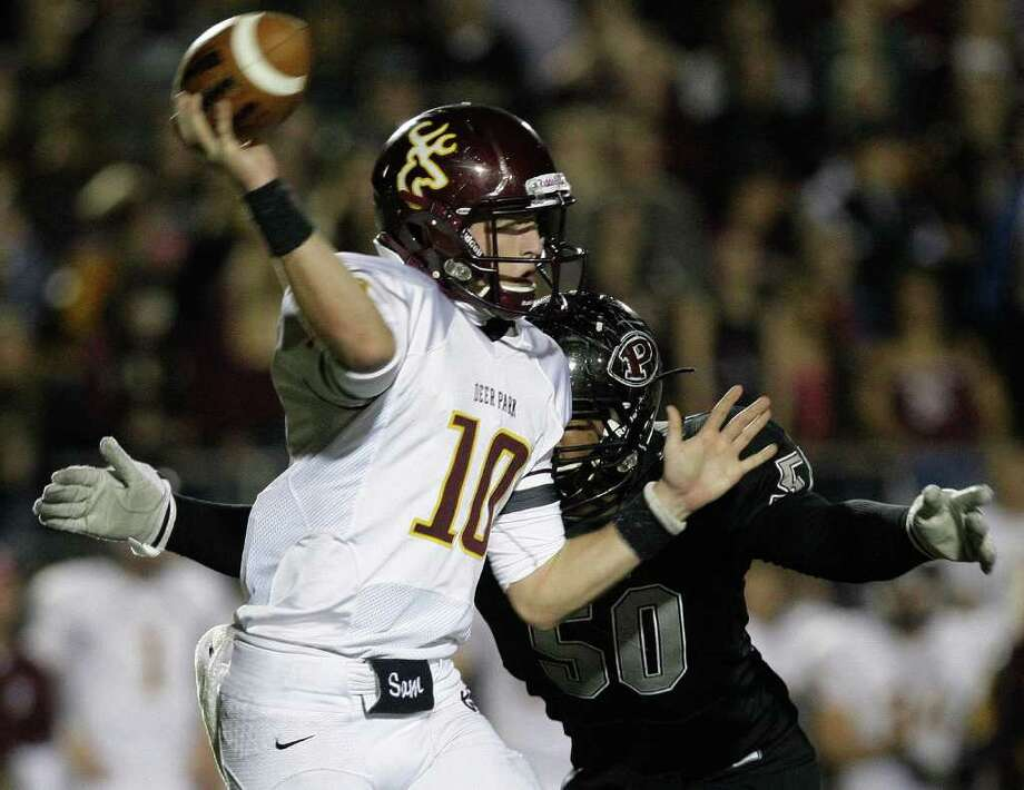 11/18/11: Quarterback Austin Rainer (10) of the Deer Park Deer passes the ball before getting hit hard by lineman Ashton Duffy (50) of the Pearland Oilers  in an area high school football playoff game at GPISD Stadium in Houston, Texas. Photo: Thomas B. Shea, For The Chronicle / © 2011 Thomas B. Shea