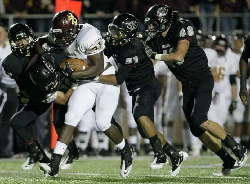 11/11/11: Running back Demetrius Banks (21) of the Deer Park Deer is gang tackled by the Pearland Oi