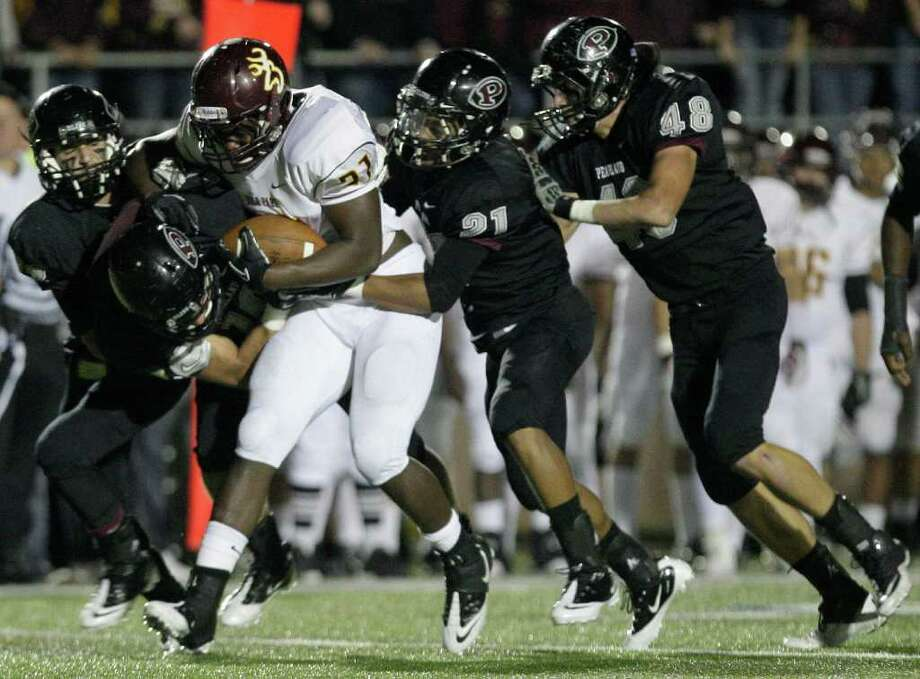 11/11/11: Running back Demetrius Banks (21) of the Deer Park Deer is gang tackled by the Pearland Oilers defense in an area high school football playoff game at GPISD Stadium in Houston, Texas. Photo: Thomas B. Shea, For The Chronicle / © 2011 Thomas B. Shea
