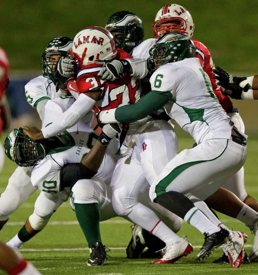 Lamar running back London kirby (32) is wrapped up by Cy Falls' Myron Jones (6) and Kevon Hunter (60)during an area high school playoff game between Cy Falls and Lamar November 18, 2011 at Tully Stadium in Houston, Texas. Photo: Bob Levey, Houston Chronicle / ©2011 Bob Levey