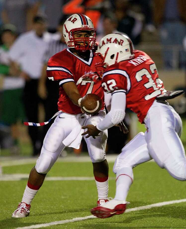 Quarterback Darrell Colbert (7) hands off to running back London Kirby (32) during an area high school playoff game between Cy Falls and Lamar November 18, 2011 at Tully Stadium in Houston, Texas. Lamar comes back for a 35-34 win. Photo: Bob Levey, Houston Chronicle / ©2011 Bob Levey