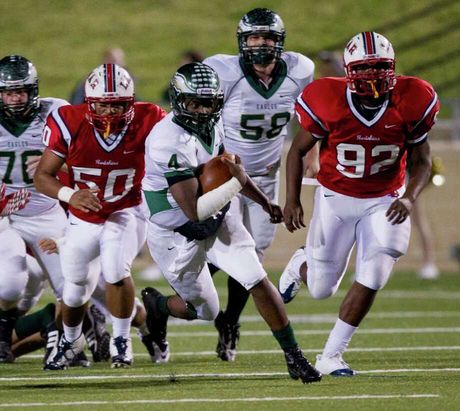 Cy Falls quarterback Troy Mitchell (4) rushes past Lamar's Jason Noble (50) and Zelt Minor (92) during an area high school playoff game between Cy Falls and Lamar November 18, 2011 at Tully Stadium in Houston, Texas. Photo: Bob Levey, Houston Chronicle / ©2011 Bob Levey