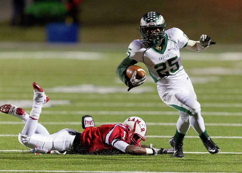 Cy Falls' Gratian Gladney (25) slips past a diving Cedric Lancaster (1) from Lamar during an area high school playoff game between Cy Falls and Lamar November 18, 2011 at Tully Stadium in Houston, Texas. Photo: Bob Levey, Houston Chronicle / ©2011 Bob Levey