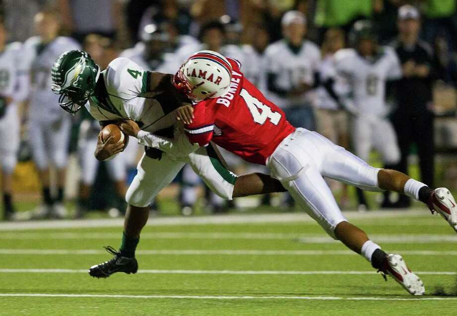 Cy Falls' Troy Mitchell (4) is tackled by Lamar's John Bonney (4) during an area high school playoff game between Cy Falls and Lamar November 18, 2011 at Tully Stadium in Houston, Texas. Photo: Bob Levey, Houston Chronicle / ©2011 Bob Levey