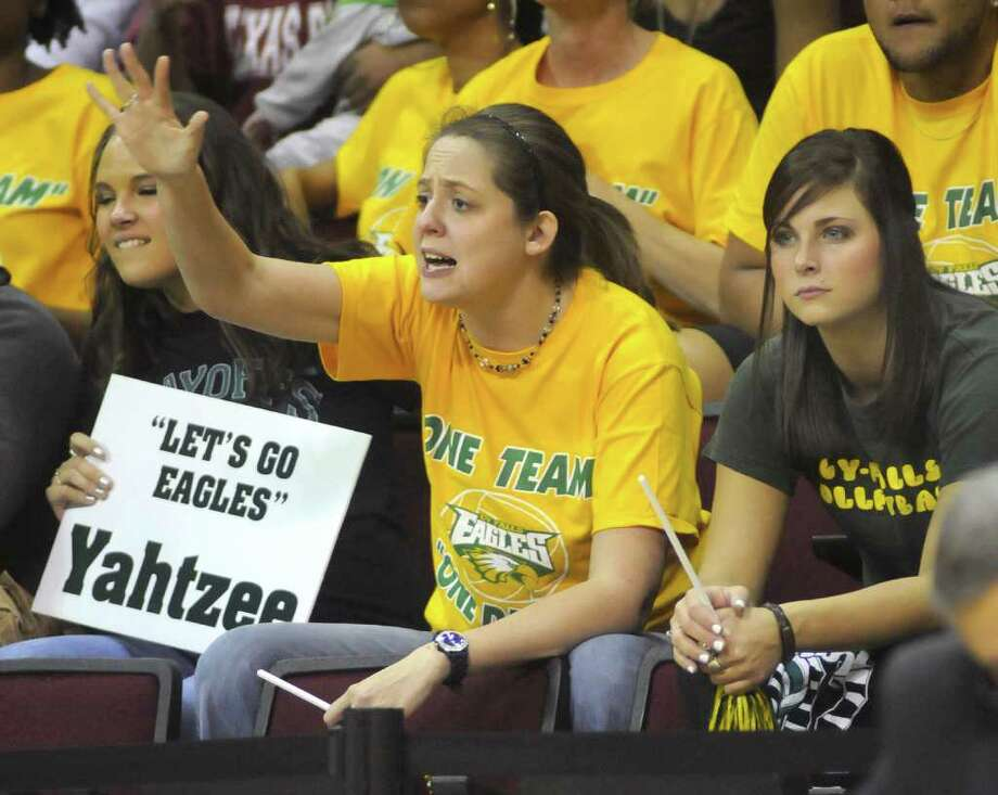 Sarah Crowe, 24, center, a former Cy-Falls volleyball player, sitting between friends and also former players Kellsey Reed, 20, left, and Caitlyn Cleveland, 18, yells to the Golden Eagles to close out the third game with just five more points during  their Class 5A state volleyball semifinal versus McKinney Boyd at Strahan Coliseum on the campus of Texas State University in San Marcos on Friday. Freelance photo by Jerry Baker    ch Photo: Jerry Baker, For The Chronicle