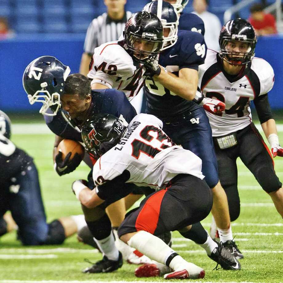 Smithson Valley running back Lawrence Mattison (left) loses his helmet as he is tackled by Lake Travis's Zach Streuling during their 4A Division I second-round football playoff game at Alamo Stadium on Nov. 18, 2011.  Lake Travis advanced to the next round with a 42-21 victory.   MARVIN PFEIFFER/mpfeiffer@express-news.net Photo: MARVIN PFEIFFER, Express-News / Express-News 2011