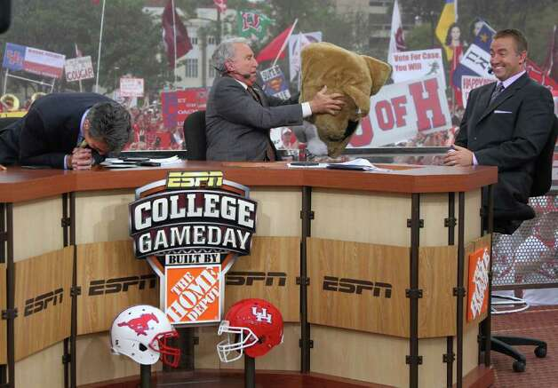 ESPN commentators Chris Fowler, Lee Corso and Kirk Herbstreit laugh as Corso pouts on a mascot head after dropping the F-bomb on the ESPN College GameDay set at the University of Houston campus Friday, Nov. 18, 2011, in Houston. Photo: Thomas B. Shea, For The Chronicle / © 2011 Thomas B. Shea