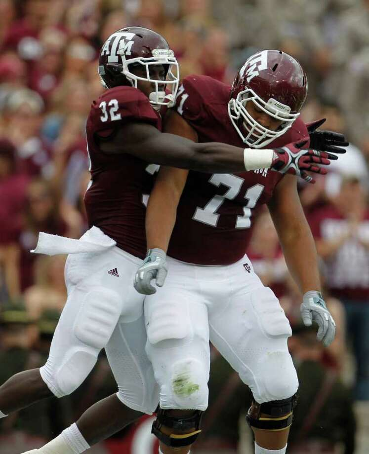 Texas A&M Aggies running back Cyrus Gray (32) celebrates his touchdown with teammate offensive linesman Brian Thomas (71) during the first half of the college football game at Texas A&M, Nov. 19, 2011. Texas A&M was leading Kansas 44-0 at the half. Photo: Karen Warren, Houston Chronicle / © 2011 Houston Chronicle