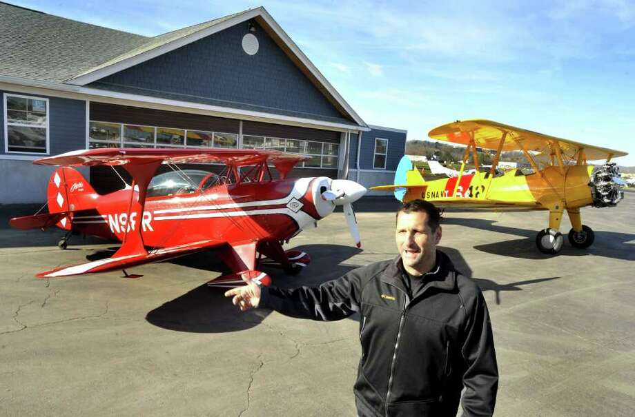 Chris Orifici talks about expanding his business, Westconn Aviation, at the Danbury Municipal Airport Saturday, Nov. 19, 2011. Two of the planes based at Westconn are on the runway behind him, a Pitts S-2B, left and an antique 1941 Boeing Stearman orignal Navy trainer. Photo: Michael Duffy / The News-Times