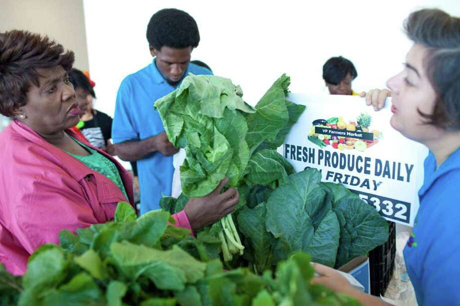 Sherray Reed, left, talks to Sera Shagoury about the collard greens on sale Friday at the Martin Luther King Jr. Community Health Clinic. The program will bring healthy, affordable food to the county's poorest neighborhoods every week. Photo: Eric Kayne / © 2011 Eric Kayne