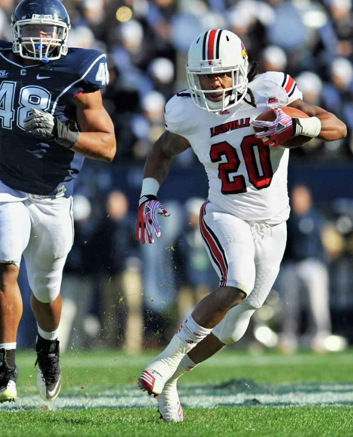 Louisville's Victor Anderson, right, breaks away from Connecticut's Trevardo Williams, left, in the first half of an NCAA college football game at Rentschler Field in East Hartford, Conn., Saturday, Nov. 19, 2011. Anderson rushed for 72 yards as Louisville beat Connecticut 34-20. (AP Photo/Jessica Hill)