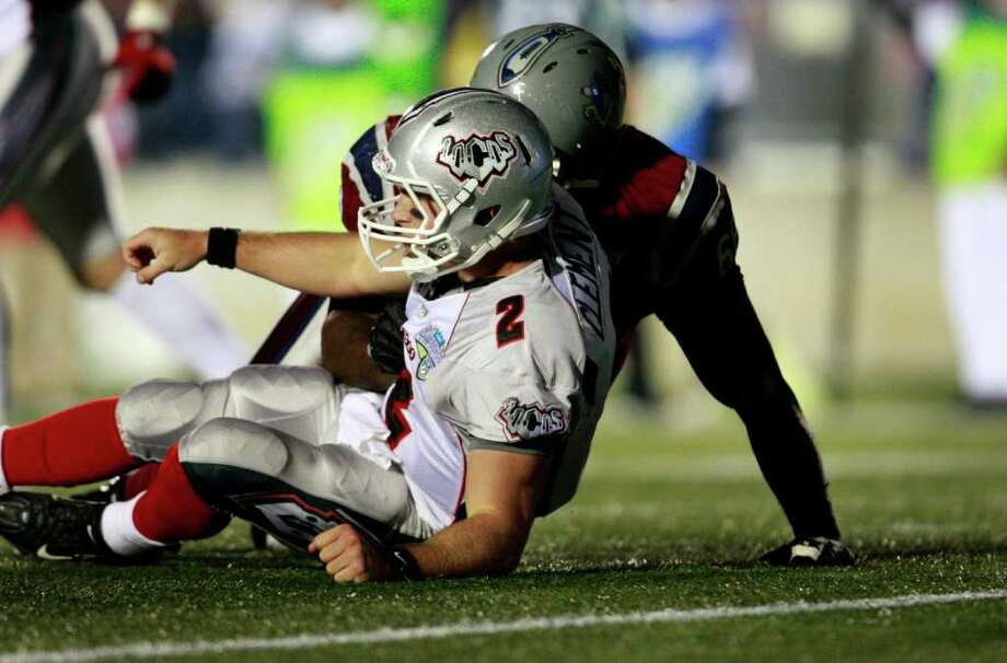 Quarterback Chase Clement, 2, of the Las Vegas Locomotives, front, is hit as he passes by Mickinley Boykin, 68, of the Virginia Destroyers during the first half of the 2011 United Football League Championship Game, Friday night Oct. 21, 2011 at the Virginia Beach (VA) Sportsplex. (AP Photo/L. Todd Spencer - The Virginian-Pilot) MAGS OUT Photo: AP