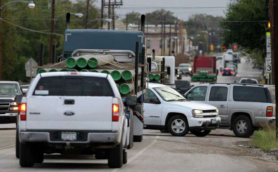 Morning traffic like this, on Thursday in Yorktown, is taking its toll on roads across the counties in the Eagle Ford shale play. Heavy trucks are tearing up the roads and bridges, and keeping older residents at home. Photo: JOHN DAVENPORT / SAN ANTONIO EXPRESS-NEWS (Photo can be sold to the public)