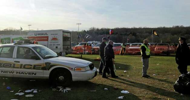 Authorities work the scene where the driver of a rental truck carrying beer kegs through a parking area before an NCAA college football game between Yale and Harvard suddenly accelerated, fatally striking a 30-year-old woman and injuring two other women, police said, Saturday, Nov. 19, 2011, in New Haven, Conn. (AP Photo/Bob Child) Photo: Bob Child, Associated Press / FR170410 AP