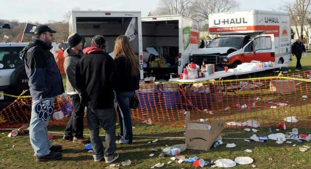People look at the scene where the driver of a rental truck carrying beer kegs through a parking area before an NCAA college football game between Yale and Harvard suddenly accelerated, fatally striking a 30-year-old woman and injuring two other women, police said, Saturday, Nov. 19, 2011, in New Haven, Conn. (AP Photo/Bob Child) Photo: Bob Child, Associated Press / FR 170410 AP