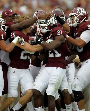 Texas A&M players mob Texas A&M Aggies defensive back Steven Terrell (21) after his interception in the second quarter of the college football game at Texas A&M, Nov. 19, 2011. Texas A&M was leading Kansas 44-0 at the half. Photo: Karen Warren, Houston Chronicle / © 2011 Houston Chronicle