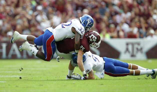 Texas A&M Aggies wide receiver Ryan Swope (25) is sandwinched between Kansas Dexter Linton (32) and Keeston Terry  (9) during the first half of the college football game at Texas A&M, Nov. 19, 2011. Texas A&M was leading Kansas 44-0 at the half. Photo: Karen Warren, Houston Chronicle / © 2011 Houston Chronicle