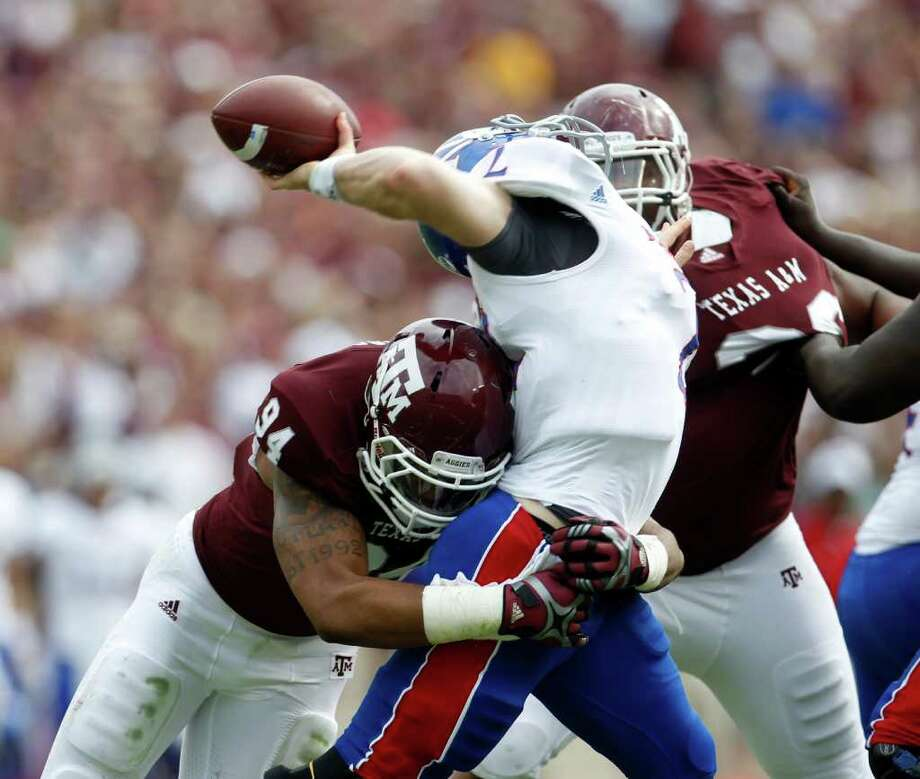 Kansas QB Jordan Webb (2) is sacked by Texas A&M Aggies linebacker Damontre Moore (94) and was off the field with an injury after getting sacked during the first half of the college football game at Texas A&M, Nov. 19, 2011. Texas A&M was leading Kansas 44-0 at the half. Photo: Karen Warren, Houston Chronicle / © 2011 Houston Chronicle