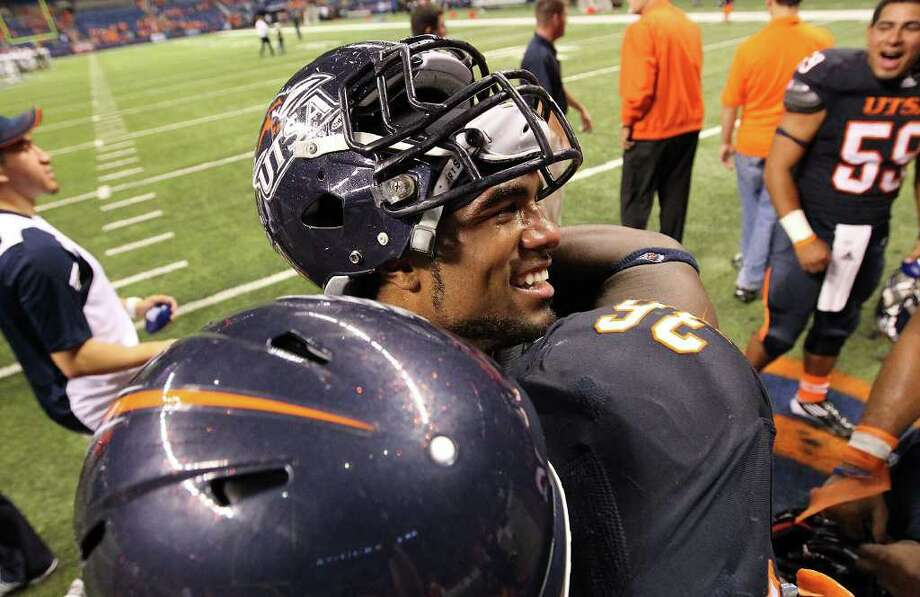 UTSA's Mark Waters (center) gets a hug from teammate Cole Hicks (26) at the end of their game against Minot at the Alamodome on Saturday, Nov. 19, 2011. Waters is a senior and played his last game as UTSA defeated Minot 49-7 for a victory to end their inaugural season. Kin Man Hui/kmhui@express-news.net Photo: Kin Man Hui, ~ / San Antonio Express-News