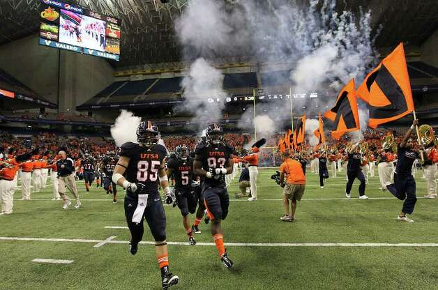 UTSA football players take the field under a cloud of pyrotechnics and cheers for their inaugural season's last game against Minot at the Alamodome on Saturday, Nov. 19, 2011. Kin Man Hui/kmhui@express-news.net Photo: Kin Man Hui, ~ / San Antonio Express-News