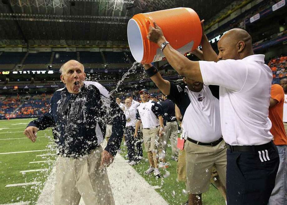 UTSA head coach Larry Coker (left) gets doused with water by assistant coach Nathaniel Jones (right) and equipment manager Scott Bajek in the closing moments of their game against Minot at the Alamodome on Saturday, Nov. 19, 2011. UTSA defeated Minot 49-7 for a victory to end their inaugural season. Kin Man Hui/kmhui@express-news.net Photo: Kin Man Hui, ~ / San Antonio Express-News