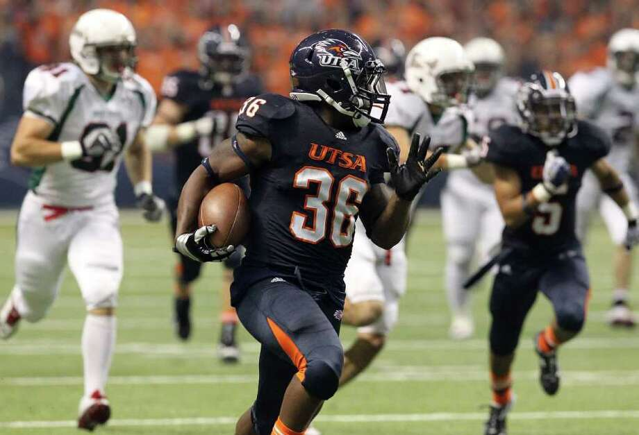UTSA's Evans Okotcha (36) looks back as he sprints away from a field of Minot defenders for a touchdown in the first half at the Alamodome on Saturday, Nov. 19, 2011. Kin Man Hui/kmhui@express-news.net Photo: Kin Man Hui, ~ / San Antonio Express-News