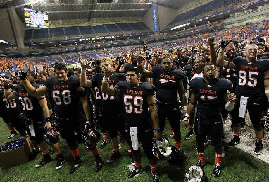 UTSA football players hold up the roadrunner gesture as the school song is played after their game against Minot at the Alamodome on Saturday, Nov. 19, 2011. UTSA defeated Minot 49-7 for a victory to end their inaugural season. Kin Man Hui/kmhui@express-news.net Photo: Kin Man Hui, ~ / San Antonio Express-News