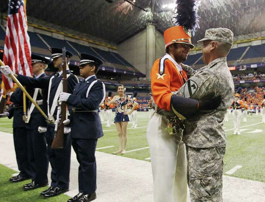 UTSA band member Christian Castro (second from left) hugs his father, U.S. Army Sgt. Luis Castro, in a surprise visit to the younger Castro before UTSA's football game against Minot at the Alamodome on Saturday, Nov. 19, 2011. Sgt. Castro returned home from a tour in Afghanistan. Kin Man Hui/kmhui@express-news.net Photo: Kin Man Hui, ~ / San Antonio Express-News